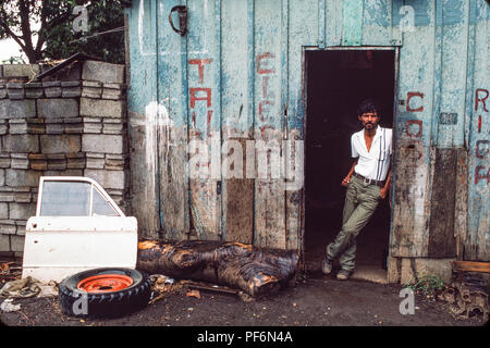Managua, Nicaragua, July 1986; A young boy rolls a car wheel that has been repaired by the run-down mechanics workshop behind. - Stock Photo
