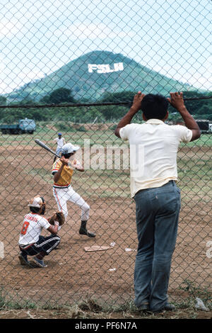 Managua, Nicaragua, June 1986; People playing baseball.  The signage of the Sandinista FSLN is visible in large letters on the opposite hillside. - Stock Photo