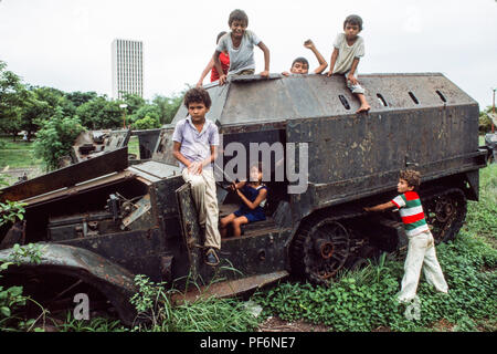 Managua, Nicaragua,  June 1986; Children play on the wrecked remains of Somoza's armoured tanks and APCs  in the centre of Managua. There were destryed by Sandinista forces in civil war against Somoza in 1979. - Stock Photo