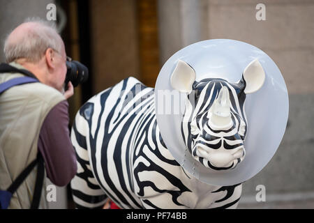 London, UK.  20 August 2018. A tourist photographs 'Going, Going, Gone', a rhino painted by Mauro Perucchetti, in Covent Garden.   21 rhinos are in place at a popular location in central London, forming the Tusk Rhino Trail, until World Rhino Day on 22 September to raise awareness of the severe threat of poaching to the species' survival.  They will then be auctioned by Christie's on 9 October to raise funds for the Tusk animal conservation charity.  Credit: Stephen Chung / Alamy - Stock Photo