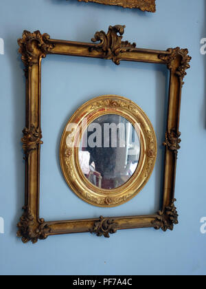 Two Gold picture frames with no pictures in the frames hanging on walls with plain background. Centre oval frame has a mirror. Property released - Stock Photo