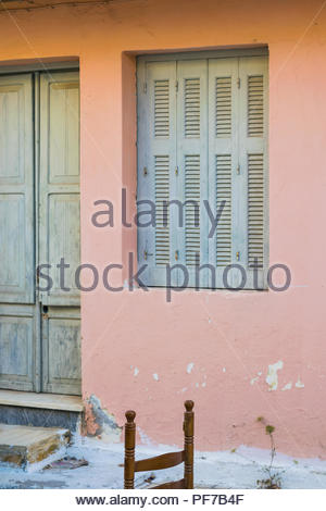 Bright colored facade .Wooden entry door , window and  one old chair on the street. - Stock Photo