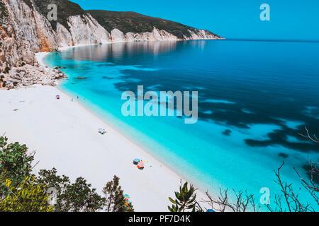 Sunny idyllic Fteri beach lagoon with limestone rocky coastline, Kefalonia, Greece. Tourists relax under umbrella near clear blue emerald turquoise sea water with dark pattern on bottom - Stock Photo