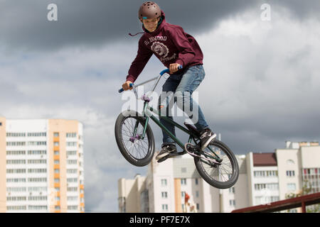 Belarus, Gomel, June 24, 2018. Central park. Extreme cycling.A dangerous trick on a bicycle against the backdrop of the city.A man in a helmet jumping - Stock Photo