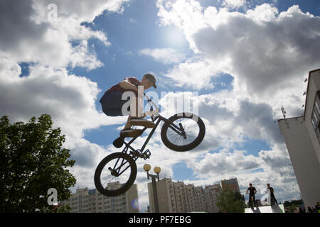 Belarus, Gomel, June 24, 2018. Central park. Extreme cycling.A dangerous trick on a bicycle against the backdrop of the city.A teenager on an extreme  - Stock Photo