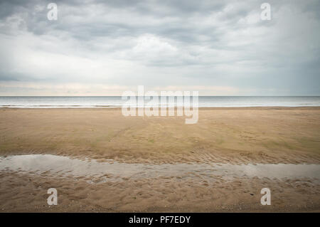 Seascape with calm beach in fall in pastel colors. Serene autumn scene resembling minimalism painting in light blue and beige tones. No people. - Stock Photo