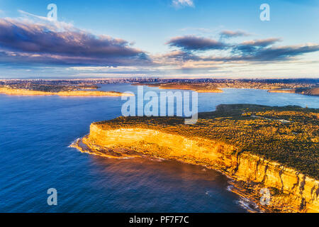 Steep edge of Sydney's north head sandstone cliffs facing Pacific ocean at the entrance to Sydney harbour in aerial elevated view towards city CBD.