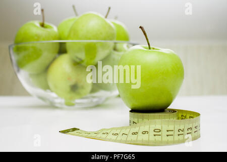 Diet, healthy eating, food and weigh loss concept. Measuring tape and green apple - Stock Photo