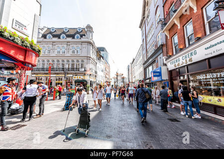 London, UK - June 24, 2018: Wide angle view of Chinatown China town Wardour street road with many crowd of people, downtown city, Chinese sign, red co - Stock Photo