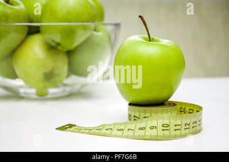 Measuring tape and green apple. Diet, healthy eating, food and weigh loss concept. - Stock Photo