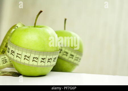 diet, healthy eating, food and weigh loss concept. Measuring tape wrapped around apple - Stock Photo