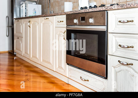 Modern wooden brown kitchen features cabinets with granite countertops and tile backsplash with closeup of dirty oven - Stock Photo
