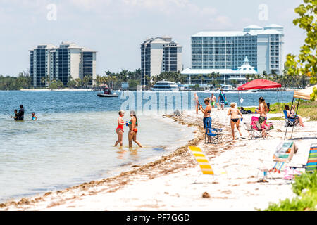 Sanibel Island, USA - April 29, 2018: Causeway beach with many people, tourists, crowd, crowded coast, coastline, chairs during sunny day - Stock Photo