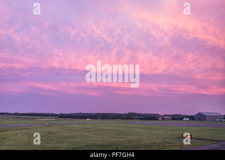 Dulles, USA - June 13, 2018: Dulles Internation Airport, IAD, runway code with colorful dramatic pink red sunset in Virginia field - Stock Photo