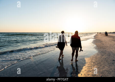 Sarasota, USA - April 27, 2018: Sunset in Siesta Key, Florida with coastline coast ocean gulf mexico on beach shore, many people silhouette walking by - Stock Photo
