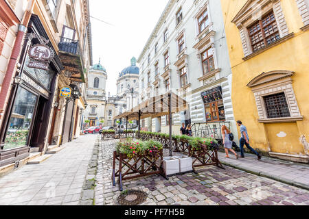 Lviv, Ukraine - August 1, 2018: Dominican church cityscape streetscape with dome in historic Ukrainian Polish Lvov city during day, outdoor cafe resta - Stock Photo