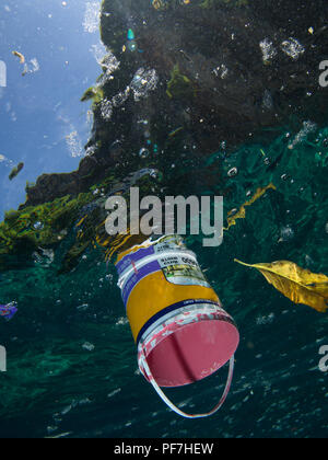 Paint bucket floating on the ocean surface, shot underwater. - Stock Photo