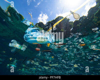 Plastic debris floating on the ocean surface, shot underwater. - Stock Photo