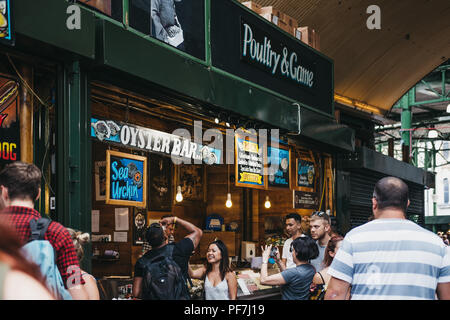 London, UK - July 24, 2018: Seller and customer at an oyster bar in Borough Market, one of the largest and oldest food markets in London. - Stock Photo