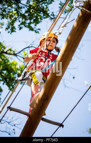 Little brave caucasian girl at outdoor treetop climbing adventure park - Stock Photo