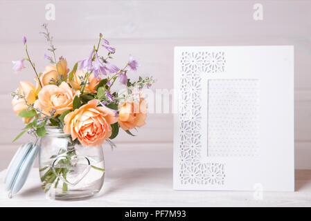 Orange English roses flowers in vase. jar and empty white photo frame on a wooden background. Mockup with copyspace. - Stock Photo