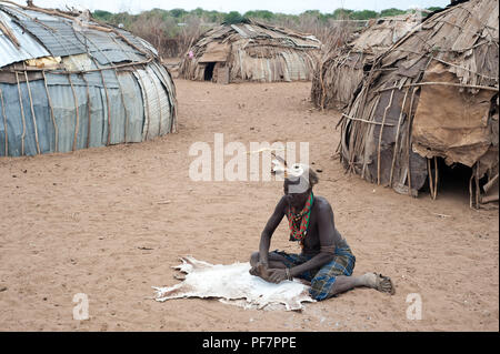 A woman is tanning a skin. She belongs to the Dassanech tribe ( Ethiopia) - Stock Photo