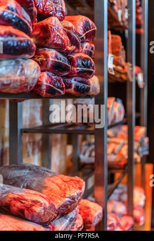 Dry aged wagyu beef and bison on display in restaurant or butcher meat shop - Stock Photo