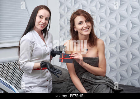 The cosmetologist gives a certificate as a gift to the client