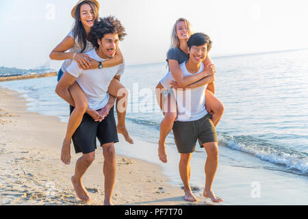 Group of friends walking along the beach, with men giving piggyback ride to girlfriends. Happy young friends enjoying a day at beach