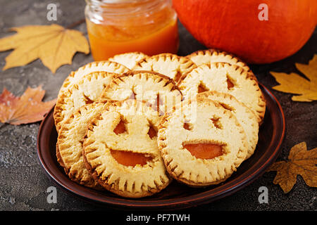 Homemade  cookies in the form as Halloween  jack-o-lantern pumpkins  on the dark table. - Stock Photo
