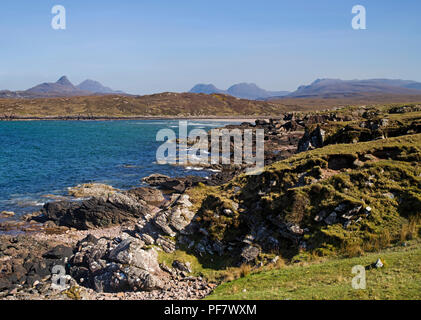 View across the rocky foreshore of Achnahaird Bay, Coigach, Scottish Highlands, to Inverpolly mountains on the horizon. - Stock Photo