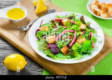delicious fresh salad of salami and mixed lettuce leaves - baby spinach, arugula, chard in a white dish on the old wooden table, top view - Stock Photo