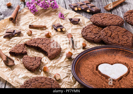Chocolate cookies, chocolate with hazelnuts on a parchment paper, close-up - Stock Photo