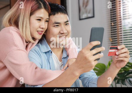 Asian couple use mobile phone shopping online with credit card together in living room at home.couple in home concept - Stock Photo