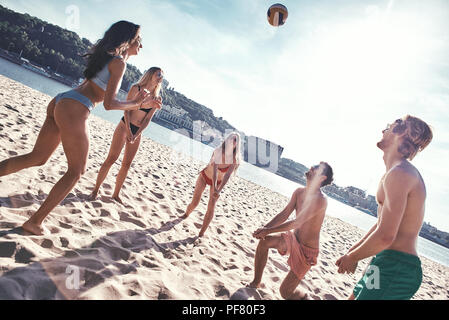 Time with friends. Group of young people playing volleyball on the beach - Stock Photo