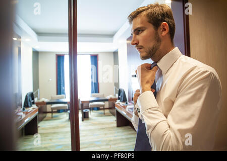 People, business,fashion and clothing concept - close up of man in shirt dressing up and adjusting tie on neck at home. - Stock Photo