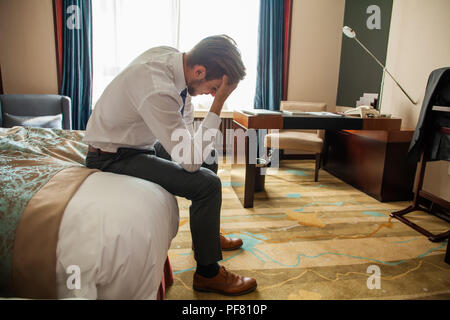 Frustrated young man in formal suit sitting on bed besides luggage bag. Businessman thinking about problems in business or at home, not feeling well, lost job, relationships or work related stress - Stock Photo