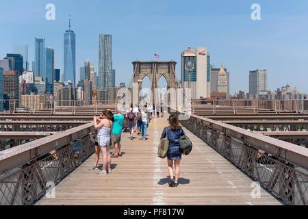 People visiting Brooklyn Bridge in New York City - Stock Photo