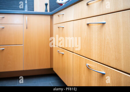Closeup of side of modern wood, wooden finish kitchen drawers, cabinets with steel handles, tile, tiled floor of brown, yellow color - Stock Photo