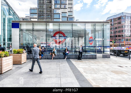 London, UK - June 21, 2018: Victoria Underground tube station outside, outdoors with modern steel, glass windows, business people, businessman, women, - Stock Photo