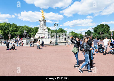 London, UK - June 21, 2018: Victoria Memorial by Buckingham Palace with many people, tourists, pedestrians walking on road, street, sidewalk, taking s - Stock Photo