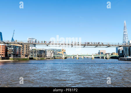 London, UK - June 22, 2018: View from boat on Thames on Millennium Bridge with people, pedestrians walking during sunny day with sunlight, clear blue  - Stock Photo