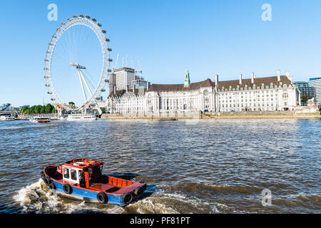 London, UK - June 22, 2018: View from Tour boat on London Eye, Waterloo Pier with many ships and closeup of one ship passing in foreground on Thames R - Stock Photo