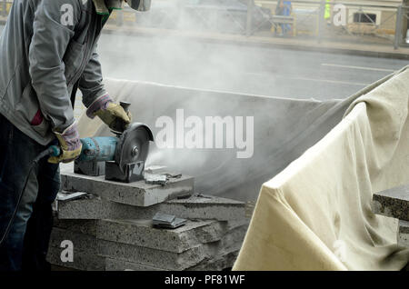 The worker cuts a big powerful angle grinder paving slabs. - Stock Photo