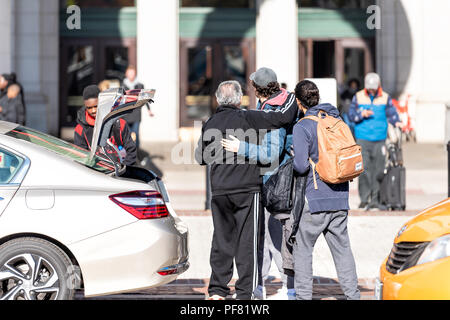 Washington DC, USA - November 23, 2017: Union Station near Columbus Circle with people, family arriving arrival hugging, happy father son standing wit - Stock Photo