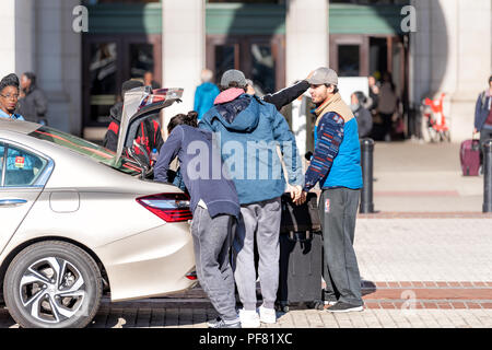 Washington DC, USA - November 23, 2017: Union Station near Columbus Circle with people, family arriving arrival hugging, happy father son with baggage - Stock Photo