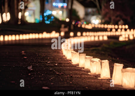 Christmas Eve candle lights, lanterns in paper bags at night along road, street, path illuminated by houses in residential neighborhood in Virginia - Stock Photo