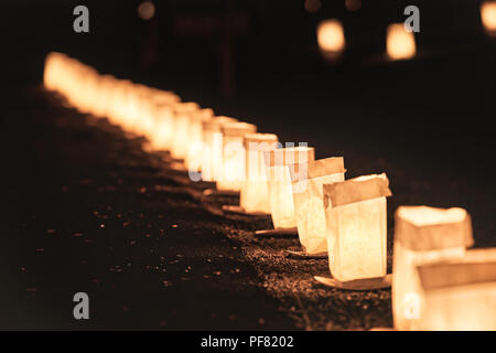Row, line of Christmas Eve candle lights, lanterns in paper bags at night along road, street, path illuminated by houses in residential neighborhood i - Stock Photo