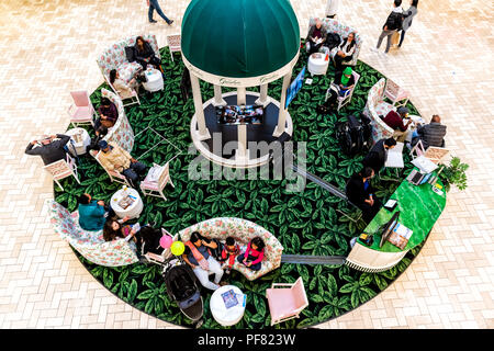 Tysons Corner, USA - January 26, 2018: High angle view on people, shoppers, customers relaxing on couches, armchairs, chairs in plaza, court of indoor - Stock Photo