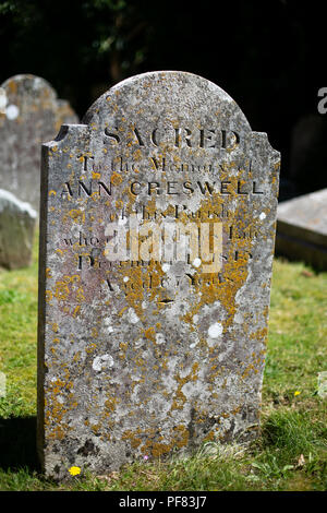 Portrait shot of an aged headstone in an english village churchyard covered in moss - Stock Photo